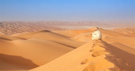 arab man in traditional outfit sitting over a Dune in